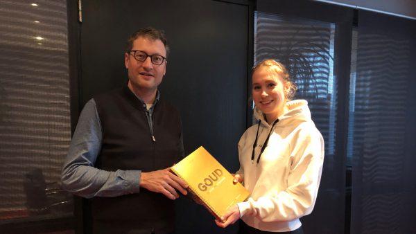 Merel Conijn overhandigt het boek GOUD.